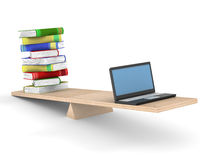 Books and laptop on scales. Stock Photo