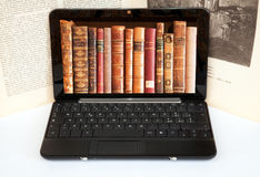 Books on laptop screen. With a paper novel  in the background Royalty Free Stock Image