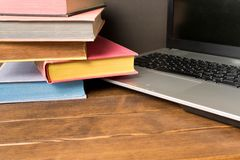 Books and laptop on wooden table. The concept of learning from b stock images
