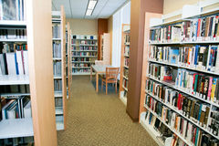 Books at Library. Many books on rows of shelves in a public library in the United States of America. A table and chairs located next to a window offer readers a Stock Photos