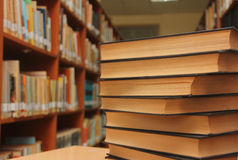 Books in library. Background in front of bookshelves Royalty Free Stock Image