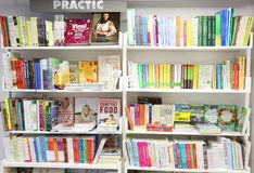 Books in library. Books placed on white shelves at the practical section Royalty Free Stock Images