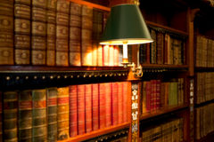 Books on library shelves. Rows of study and reference books on wooden library shelves or bookcases Stock Image