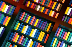 Books on library shelves. Diagonal view of colorful books on library shelves stock images