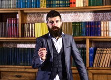 Books and literature. Speaker with calm face stands in vintage interior. Bearded man in elegant suit near bookcase. Mature man with long beard. Discussion Stock Photography