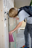 Books in Locker. Young middleschool student putting a book into his school locker royalty free stock image