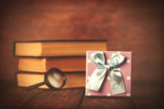 Books with loupe and gift box Stock Photos