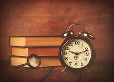 Books with loupe and retro alarm clock Stock Photos