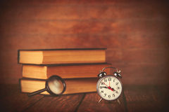 Books with loupe and retro alarm clock Royalty Free Stock Photography