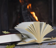 Books lying on a table in front of a fireplace Royalty Free Stock Images
