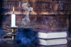 Old books of magic and witch pot with smoke and candle royalty free stock image