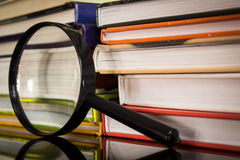 Books and magnifier stock images
