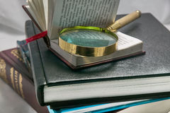 Books, magnifying glass Stock Photos
