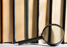Books and magnifying glass Stock Images
