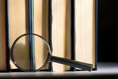 Books and magnifying glass Stock Image