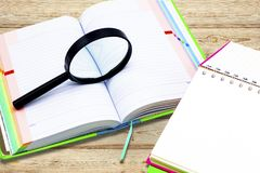 Books and magnifying glass on wood table, education and back to school subject,Clipping path stock photography