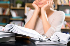 Books and manuals are lying on the desk. Lots of studies. Close up of a few books and reading glasses resting on the library table stock photos