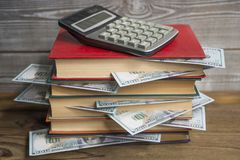 Books with money dollar banknotes, calculator. stock image
