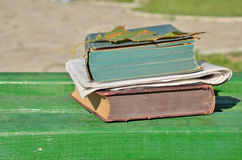 Books and newspapers on wooden bench Stock Image