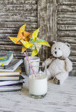 Books, notebooks, journals, handmade paper pinwheels and a glass of milk - baby workplace Stock Images