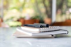 Books and notebooks with pens on the table with blur green nature stock photo