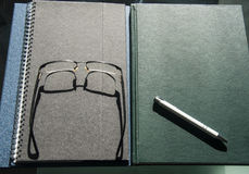 Books and notebooks piled up with pen and glasses Stock Photo