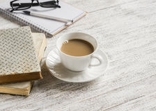 Books, open a blank notepad and a cup of tea with milk. On white wooden table Stock Photos