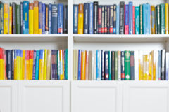 Books out of focus background texture. Rows of books in bookshelves, out of focus, bright and colorful, library or office interior background texture, copy or Stock Photo