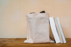 Books outside of cloth bag on wooden table. Books outside of cloth bag on wood table Stock Photo