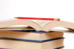 Books with Pencil. Stack of books with one open with a pencil resting on it, set against a white background Stock Photos