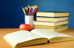 Books, pencils and apple on the table Stock Photography