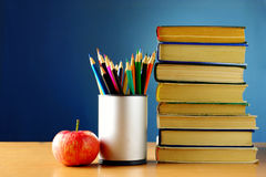 Books, pencils and apple on the table Royalty Free Stock Image