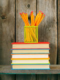 Books and pencils on a wooden shelf. Stock Image