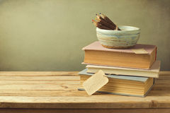 Books and pencils on wooden table in vintage style. Over green blur background Royalty Free Stock Photo