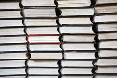 Books pile. Many black books rows only  one is red Royalty Free Stock Photos