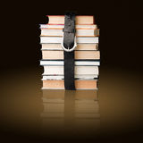 Books pile with belt. Many books pile with black leather belt Royalty Free Stock Image