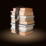 Books pile with belt. Many books pile with black leather belt Stock Image