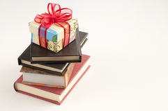 Books and present. Pile of books and a present on a white background Stock Photos