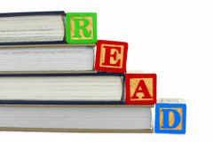 Books and READ blocks. Books with toy wooden blocks spelling READ over white Stock Images
