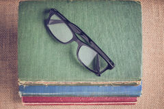Books and reading glasses on vintage Burlap background with Inst Royalty Free Stock Photography