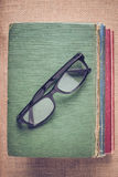 Books and reading glasses on vintage Burlap background with Inst Royalty Free Stock Images