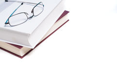 Books and reading glasses on white Stock Photography