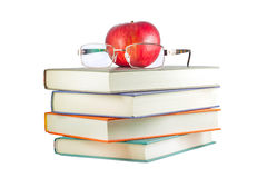 Books with red apple and glasses on a white background Royalty Free Stock Photo