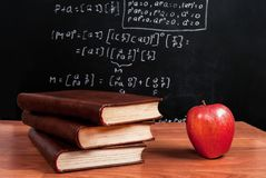 Books and red apple on a wooden table in math class in the classroom. Red Apple and books on wooden table and school blackboard with mathematical equations in stock image