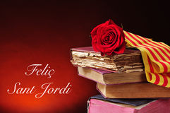 Books, red rose and the text Felic Sant Jordi, Happy Saint Georg Royalty Free Stock Photo