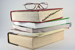 Books - Reference and Education. Dictionary, word finder, reference and resource books stack up for use under a set of eyeglasses Royalty Free Stock Photos