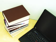 Books Research with Laptop. A pile of books on a desk together with a laptop computer. Suitable for various education, university, or library reading and Royalty Free Stock Images