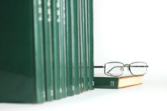 Books in a row. Row of green books and reading glasses resting on top of last book Royalty Free Stock Photo
