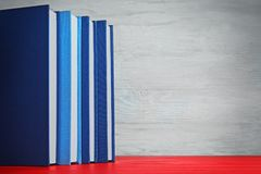Books in a row on red   table. Books in a row on red wooden table Stock Image