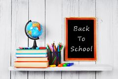Books and school tools on wooden shelf. Royalty Free Stock Images